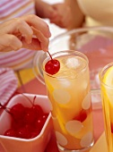 Children's punch with cocktail cherries and ice cubes