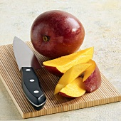 Whole Ripe Mango on a Cutting Board with Mango Slices, Knife