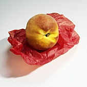 A Single Peach on Red Tissue Paper on White Background