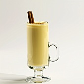 Glass Mug of Eggnog with Nutmeg and Cinnamon Sticks on White Background