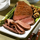 Partially Sliced London Broil on a Platter with Asparagus and Mushrooms