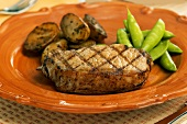 Grilled pork chop with potatoes and sugar snap peas