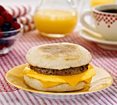 Sausage Egg and Cheese Breakfast Sandwich on Table, Coffee and Orange Juice