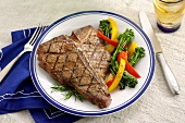 Grilled Steak Served with Bell Peppers and Broccoli Rabe, On a Plate with Flatware