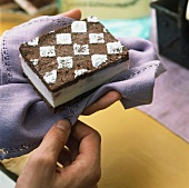 Hands holding an ice cream sandwich on napkin