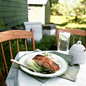 Salmon fillet with honey, pak choi & rice on outdoor table