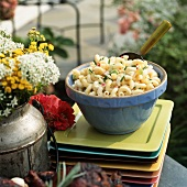 Pasta salad in blue bowl on pile of plates (outdoors)