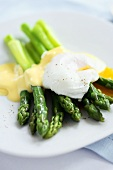 Poached Egg with Hollandaise Sauce Over Asparagus on White Plate