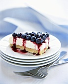 Slice of Cheesecake with Blueberry Topping on Stack of White Plates, Forks