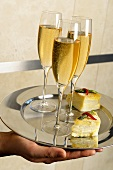 Hand Holding a Silver Tray with Glasses of Champagne and Appetizers