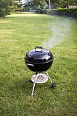 Charcoal Grill with Smoke Coming Out if the Lid Outside on the Lawn
