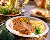 Grilled New York Steak with Fettucini on Table with Side Salad and Cheesecake