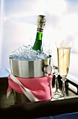 Bottle of sparkling wine in champagne bucket, glasses on tray