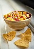 Mango salsa in bowl, tortilla chips beside it