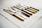 Various butter knives on fabric napkin