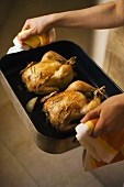 Hands holding roasting dish containing two chickens