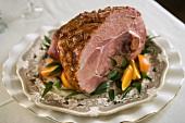 Glazed Baked Ham on a Platter with Orange Wedges
