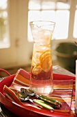 Iced water with lemon slices in carafe, spoons beside it