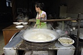 Asian Woman Stirring Large Soup Caldron