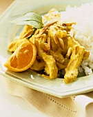 Curried Chicken with Almonds and Golden Raisins Over Rice; Orange Wedge Garnish