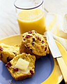 Cranberry Corn Muffins on a Plate; One Sliced in Half with Butter Melting on It; Glass of Orange Juice