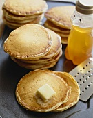 Stacks of Pancakes on a Griddle; Butter Melting on One Stack; Spatula and Honey Bear