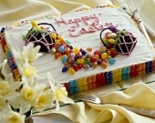 Happy Easter Cake Decorated with Jelly Beans and Easter Candy; On a Platter with Forks