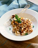 Wagon Wheel Pasta with Fresh Tomato Sauce with Olives and Feta Cheese in a White Bowl; Fork
