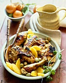Grilled Chicken with Orange Sections and Green Olives on a Plate; Wooden Fork and Spoon