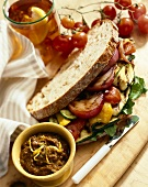 Grilled Vegetable Sandwich on Crusty White Bread; Small Bowl of Vegetable Spread; Tomatoes