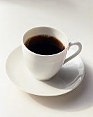 White Cup of Coffee on a White Saucer on a White Background