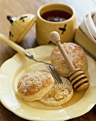 Two Fork Split Biscuits on a Plate; One Split in Half with Honey; Honey Dipper and Fork