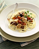 Spaghetti Tossed with Tuna, Olives and Fresh Tomatoes on a White Plate with a Fork