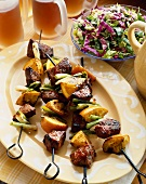 Beef, Orange and Green Onion Kabobs on a Platter; Side Salad and Mugs of Beer