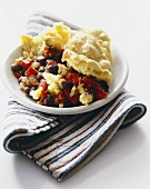 Serving of Black Bean Casserole with Corn Bread Topping in a White Bowl