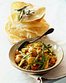 Bowl of Curried Vegetables with Spoon; Stack of Flat Bread
