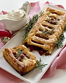 Cranberry Strudel Broken on a Platter; Pitcher of Whipped Cream