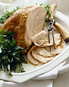 Partially Sliced Roast Turkey Breast on a Platter with Carving Utensils