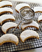 Shortbread Crescent Cookies on a Cooling Rack with Powdered Sugar; Sifter