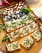 Rectangular Pizza with Rows of Assorted Toppings; Partially Sliced; On Cutting Board