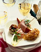 Appetizer Plate with Four Assorted Hors d'oeuvres; Glasses of White Wine