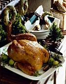 Whole Roast Turkey on a Platter with Figs; Stack of Serving Dishes