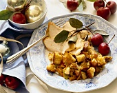 Two slices of roast turkey, bread stuffing and apples on a plate