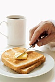 Hand spreading butter on toast, mug of coffee behind