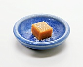 Square of caramel with sea salt in a blue dish