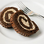 Two slices of chocolate Swiss roll with vanilla cream