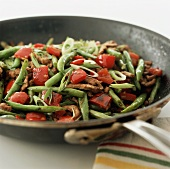 Strips of beef with peppers and green beans in frying pan