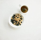 Muesli with blueberries and cup of tea