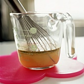 Stock in a measuring jug with a whisk