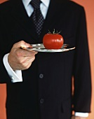 Waiter holding fresh tomato on silver tray